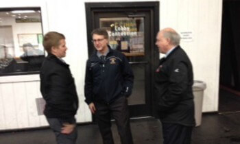Brighton coaches Kurt Kivisto, left, an Paul Moggach talk with Hancock coach Dan Rouleau before Friday's game at the Houghton County Arena in Hancock.