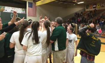 Howell players and coach Tim Olszewski, in green shirt, break a huddle after cutting down the net on Friday night.