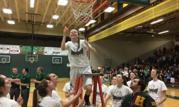 Howell's Lexie Miller celebrates after cutting a piece of the net following the Highlanders' win Friday night. Howell beat Brighton, 43-28, clinching its first KLAA West title since 2010. (Photo by Tim Robinson)