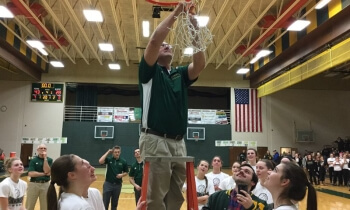 Howell coach Tim Olszewski finishes cutting down the net after his team downed Brighton, 43-28, to win the KLAA West title on Friday.