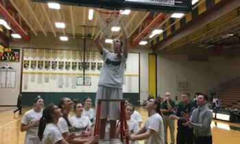 Erin Honkala helps cut down the net after Howell's 42-27 overtime win over Hartland for the Lakes Conference title Friday. (Photo by Tim Robinson)