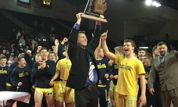 Hartland coach Todd Cheney holds the Division 1 state championship trophy high after the Eagles won it Saturday in Mount Pleasant. It was the first state team wrestling title in school history/.