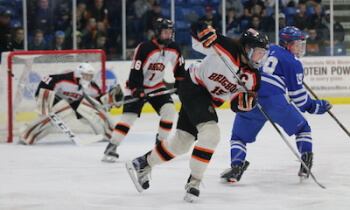 Nick Foran (15) and Brody White (16) move the puck up the ice against Detroit Catholic Central Saturday night. (Photo by Karen Kivisto)