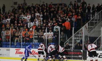 Brighton's Jake Crespi (24) and Lee Pietila (9) battle for the puck in front of the Bulldogs student section during Saturday's game. (Photo by Karen Kivisto)