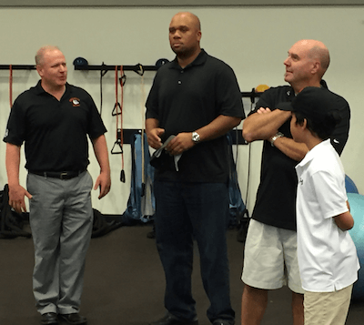 Brighton superintendent Greg Gray, far left, talks with former Detroit Lion Kerlin Blaise Monday night in the school's strength and  conditioning center as BAS board member Bill Trombley and Trombley's son Liam look on. (Photo by Tim Robinson)