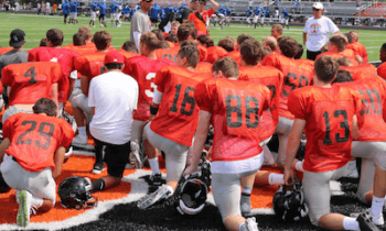 Brighton coach Brian Lemons talks to his team after a scrimmage last week. The Bulldogs will play Detroit East English at Michigan Stadium today. (Photo by Tim Robinson)