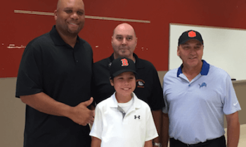 Brighton Area Schools board member Bill Trombley, back row middle, and son Liam pose with former Detroit Lions Kerlin Blaise (left) and Eddie Murray at Brighton High School on Monday. (Photo by Tim Robinson)