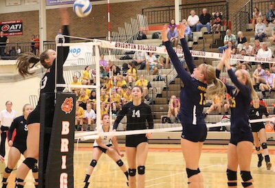 Gabrielle Tschannen (left), goes for the kill as Hartland's Megan Acs (13) and Whitney Collum defend during Tuesday's match. (Photo by Tim Robinson)