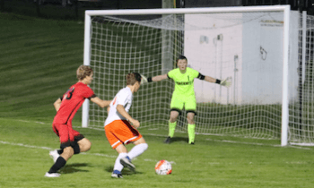 Brighton's Thomas Stanis advances on Pinckney keeper Riley Alexander as Connor Wolschlager defends in the second half on Tuesday. Stands scored the first goal for the Bulldogs in a 4-0 victory. (Photo by Tim Robinson)