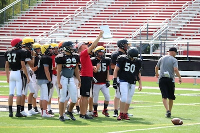 Jakob Gailitis holds up a play for his offense during a practice last month. Pinckney will look to improve to 3-0 tonight as the Pirates play host to Livonia Franklin. (Photo by Tim Robinson)