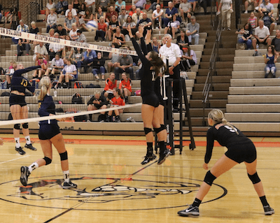 Hartland's Megan Acs (13, left) goes up for a kill as Brighton's Gabrielle Tschannen (13) and Celia Cullen (14) go up to block during Tuesday's match. The Bulldogs won in four sets. (Photo by Tim Robinson)