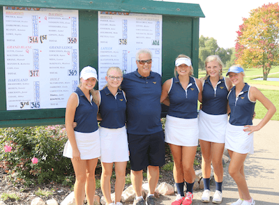 Hartland golfers and coach Mike Joseph pose in front of the leaderboard after Wednesday's Division 1 golf regional. Hartland finished third as a team, earning its first-ever berth in the state meet, which will be held next week in East Lansing. (Photo by Tim Robinson)