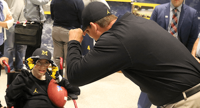 Michigan football coach Jim Harbaugh, right, helps Larry Prout Jr. adjust his baseball cap after Larry joined the Wolverines on Oct. 11. (Photo by Tim R obinson)