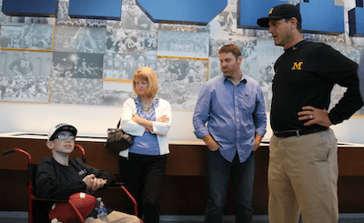 Larry Prout Jr., left, talks with Michigan coach Jim Harbaugh before an event in which Larry became an honorary Wolverine in October. Larry's father, Larry Prout Sr., is second from right. (Photo by Tim Robinson