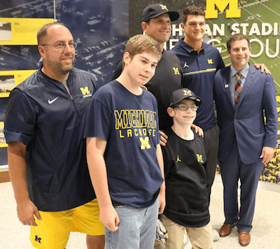 "Larry Prout Jr. poses with his friend Brendan RAndolph, who has been drafted by the Michigan lacrosse team. Behind them are, from left, lacrosse coach John Paul, football coach Jim Harbaugh and football players John O'Korn and De""Veon Smith. (Photo by Tim Robinson)"