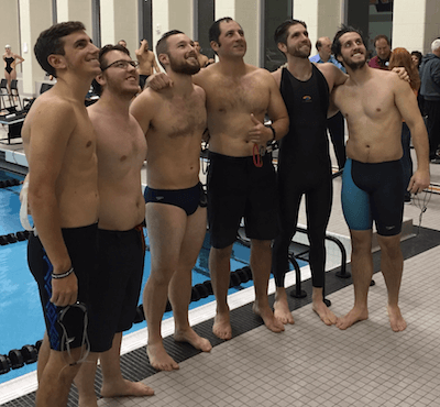 A group of former Brighton swimmers, in a variety of swim trunks, pose for a photo during Wednesday' memorial for the late Tim McInnis, a longtime fixture in the Brighton swim program who died in September. (Photo by Tim Robinson)