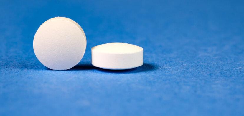 White pharmaceutical pills on blue background